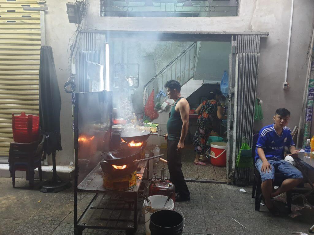 En mann steker mat i en wok på fortauet i Saigon