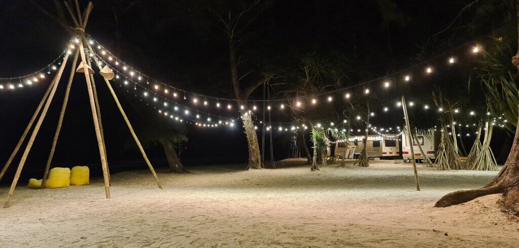 Strandcamping pyntet med lys om natten